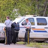 RCMP officers take down information  outside a residence on Spruce